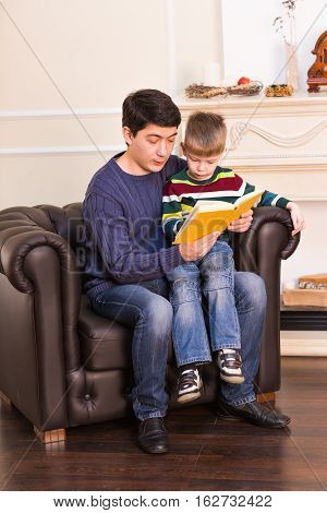 Portrait of happy parent and his son reading fairy tailes.