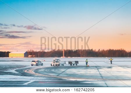Airport Marshal Team Signaling For Aircraft Controls In International Airport In Early Morning With Beautiful Sunrise Dramatic Sky. Ground Crew Signals Airport. Winter Season.