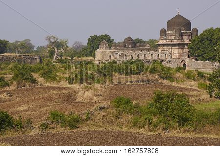 MANDU, MADHYA PRADESH, INDIA - NOVEMBER 18, 2008: Darya Khan's tomb in the hilltop fortress of Mandu. Building with central dome and a smaller dome on each corner in a walled compound. 16th Century AD