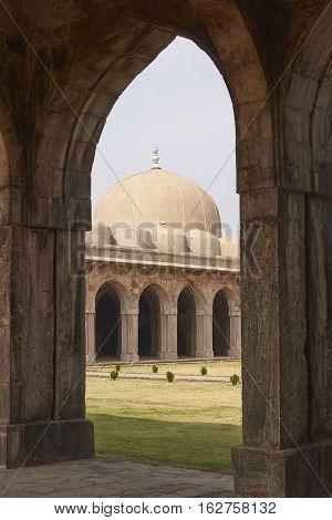 MANDU, MADHYA PRADESH, INDIA - NOVEMBER 18, 2008: Inner courtyard and covered prayer hall of the ancient mosque of Ashrafi Mahal Mosque in the hilltop fortress of Mandu in Madya Pradesh, India. 15th Century AD