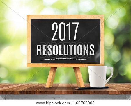 2017 Resolutions Word On Blackboard With Easel On Brown Wood Table Top With Sun And Blur Green Tree
