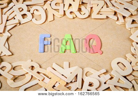 wood letters as FAQ abbreviation frequently asked questions on wooden background.