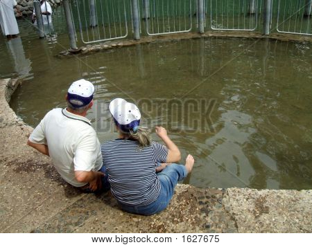 Couple Sitting With Their Feet In Jordan River In Israel