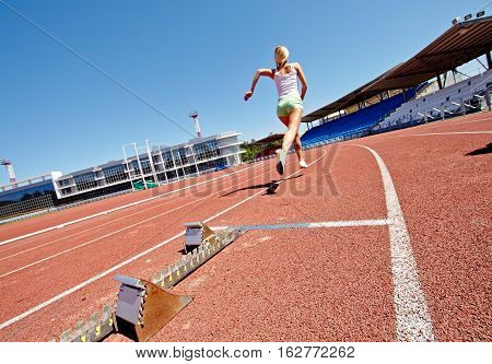 Rear view of young woman running on a track