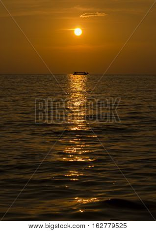 sunset on the lake with a boat on the horizon in warm colors