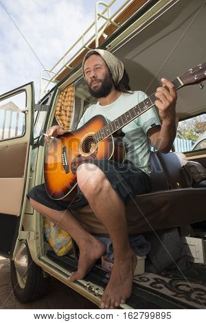 A man sits with his guitar and sigarette in hand inside his classic combi van
