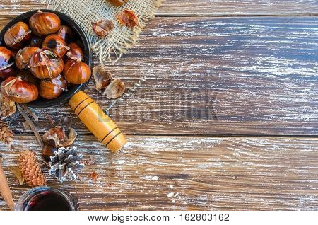 Delicious roasted chestnuts on ceramic bowl and glass of red wine on old wooden table bottle of wine fir cone cork and vintage corkscrew in the background. Top view. .Copy space