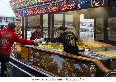 Istanbul Turkey - March 29 2013: Eating Grilled Fish Sandwich in Eminonu. The first thing that comes to mind when thinking of Istanbul is Eminonu-Karakoy and the places selling grilled fish sandwiches on the bank of Golden Horn there. Men wearing richly d