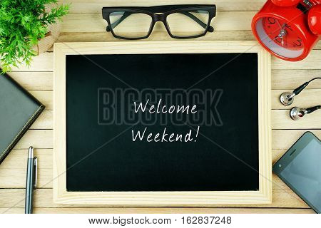 Top view of earphone, calculator, alarm clock, spectacle, notebook, pen, smartphone and chalkboard written with WELCOME WEEKEND.