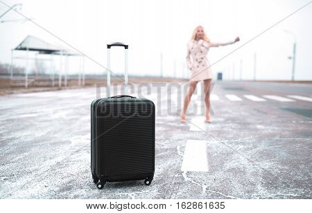 Pretty Young Woman Hitchhiking Along A Road. Selective Focus On Suitcase, Travel Concept
