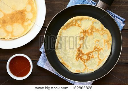 Freshly made crepe in frying pan with a stack of crepes and strawberry jam on the side photographed overhead with natural light