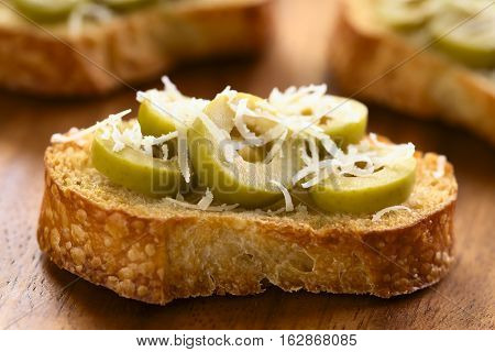 Crostini with green olive slices and freshly grated parmesan-like hard cheese photographed with natural light (Selective Focus Focus on the front of the first olive slices)