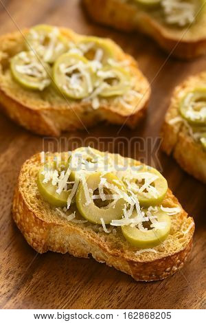 Crostini with green olive slices and freshly grated parmesan-like hard cheese photographed with natural light (Selective Focus Focus one third into the image)
