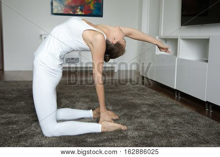 Sporty young woman practicing yoga, sitting in Camel exercise, Ustrasana pose, working out, wearing white sportswear, indoor full length, home interior background