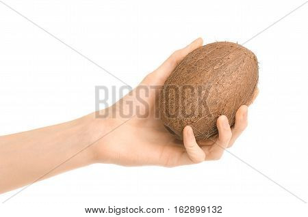Healthy Eating And Diet Topic: Human Hand Holding A Ripe Brown Coconut Isolated On White Background