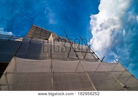 scaffolding of iron pipes and sheeting to prevent introspection around a building undergoing restoration work renovation or new construction