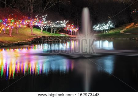 View of a pond with a fountain surrounded by trees with Christmas lights