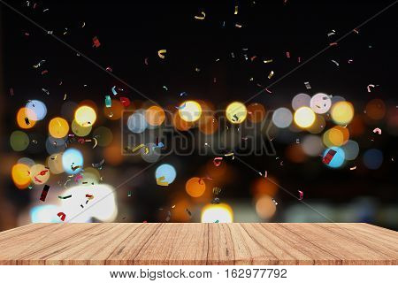 Empty wood table and ribbon motion multicolored night light bokeh for Christmas New Year background. with copy space add text