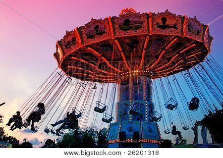 Merry-go-round spinning with people against the sunset sky