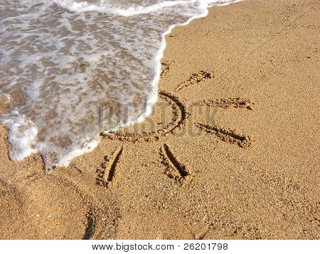Finger drawn sun on sand being washed by sea wave
