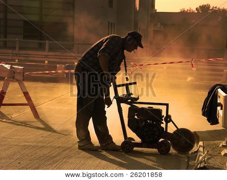 Silhouette of construction worker working with concrete cutter