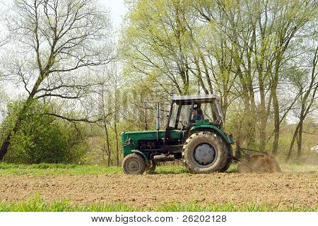 Farm tractor plowing arable field in the springtime