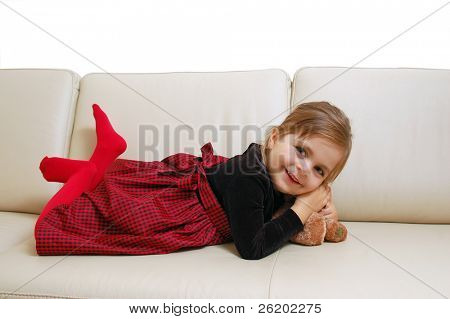 Little cute girl posing happily on sofa with her teddy bear