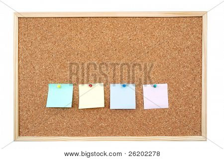 Four colorful blank post-it notes affixed to the corkboard - isolated on white