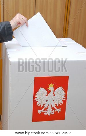 Voter casting vote into ballot box in Parliamentary election in Poland
