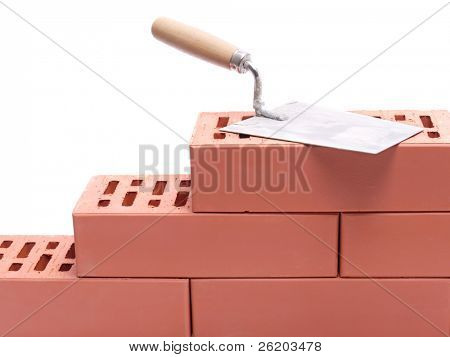 Stainless steel trowel laying on unfinished brick wall isolated on white