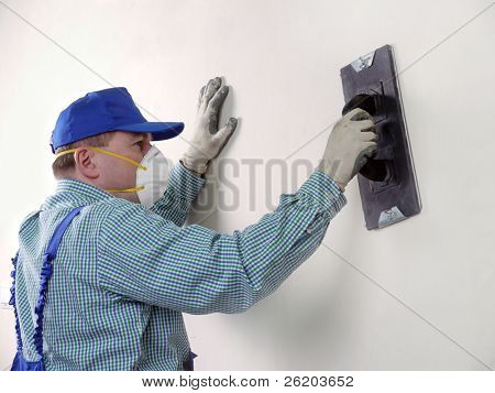 Plasterer smoothing out wall with trowel
