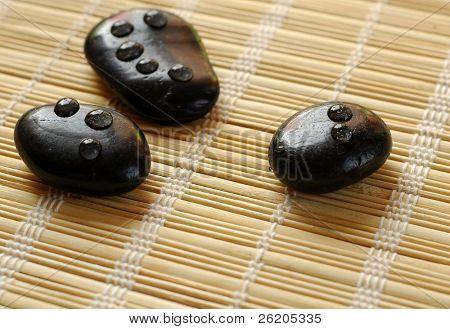 Massage stones on bamboo mat
