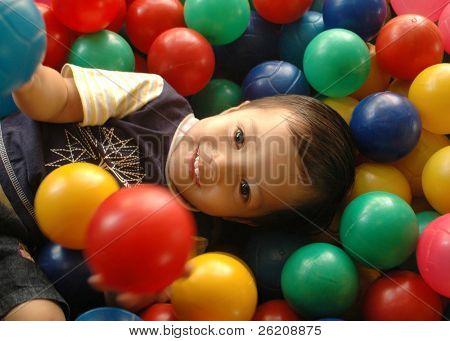 Little boy having fun time in balls pool