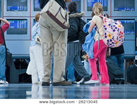 Travelers and businesspeople glance at the departure and arrival information at an airport