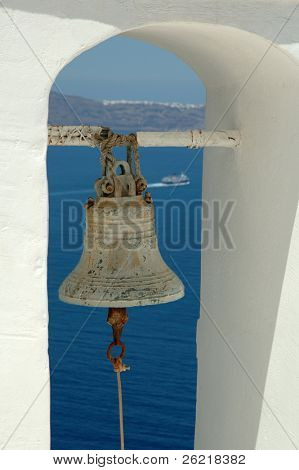 Bell in belltower with ship in the background on the Greek island of Santorini