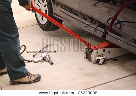 Mechanic working on car using various tools to change tires on a vehicle.