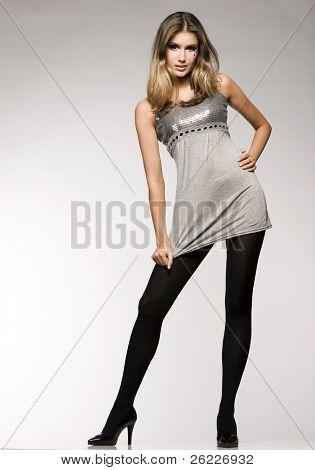 beautiful blond model in grey lucid dress posing on grey background