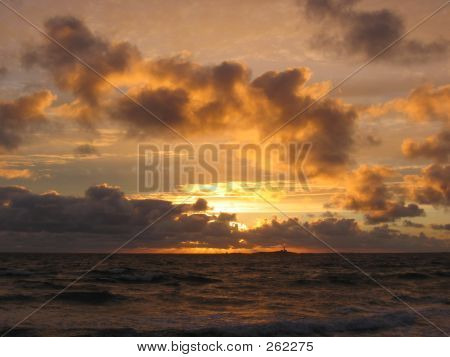 A Sunset Over The Sea With A Lighthouse In The Horizon