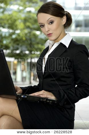 young and attractive businesswoman working on laptop outdoors