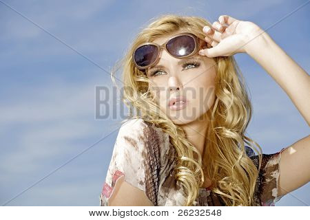 Portrait of beautiful blond Girl in Sonnenbrille auf Himmel Hintergrund blau