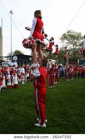 Strong male cheerleader lifting a female