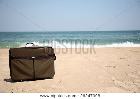 Conceptual shot of vacation travel with a suitcase on the beach