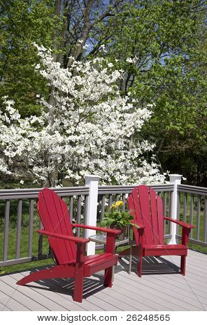 Red adirondack chairs on a grey deck
