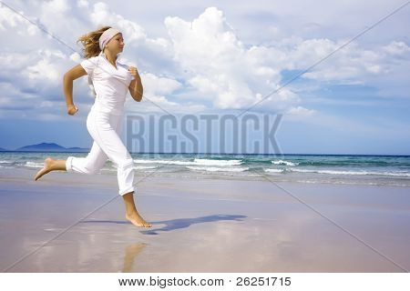 Young woman is running near the ocean. Space for copy