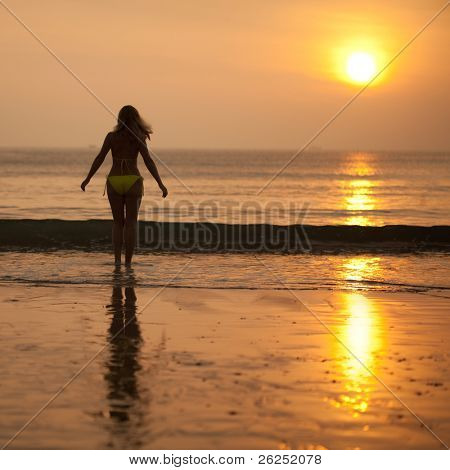 Woman near the ocean at sunrise time