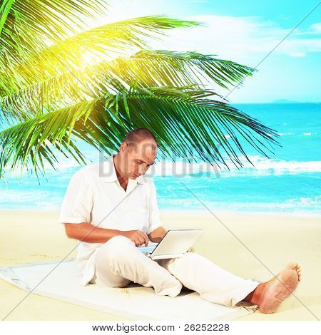 Man with netbook working near the ocean under palmtree.