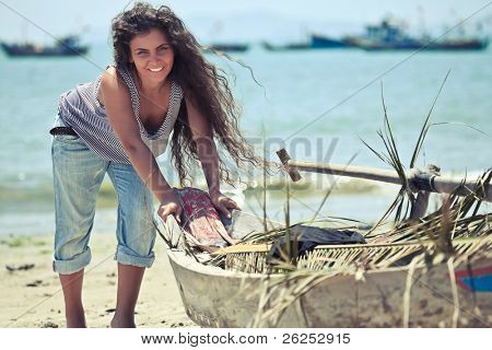 Young beautiful fisherwoman with boat on the beach