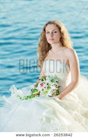 Beautiful bride sitting on a rock in a sea