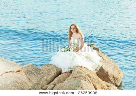 Beautiful bride sitting on a rock in a sea