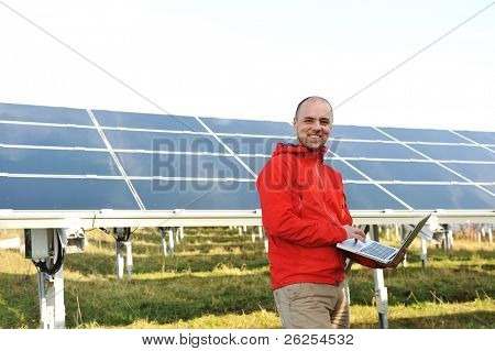 Engineer using laptop, solar panels in background